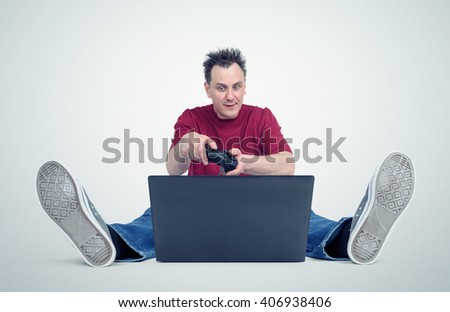 Gamer sitting on the floor playing on laptop - stock photo