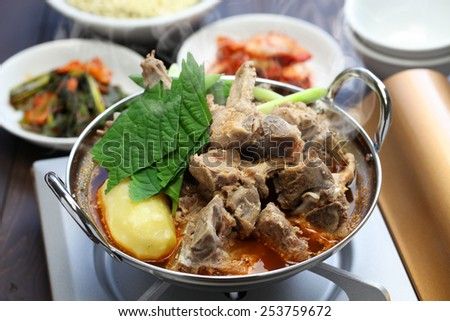 gamjatang, pork bone and potato soup, korean cuisine, simmering on the portable gas stove - stock photo