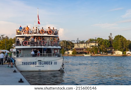 GANANOQUE, ONTARIO - SEPTEMBER 5, 2014: Cruise ship with tourists in the harbor and a historic hotel in Gananoque, Ontario - stock photo