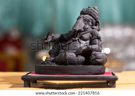 Ganesha Hindu God statue close up on yellow paper and bokeh background - stock photo