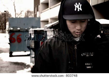 Gangsta rapper (Chuckie Ack of 21 Clipz) making a phone call in a back alley. - stock photo