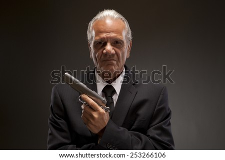Gangster Gunman Enforcer   Portrait of mature criminal in suit with handgun, looking serious and in charge. - stock photo