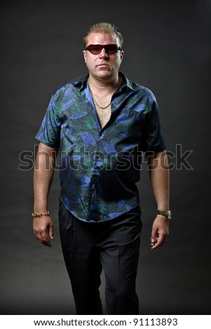 Gangster mafia man with sunglasses in casual outfit looking tough isolated on dark background