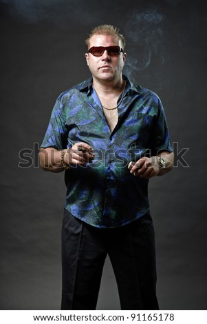 Gangster mafia man with sunglasses in casual outfit smoking cigar looking tough isolated on dark background