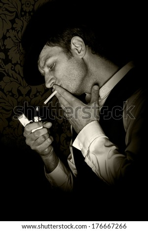 Gangster man. A gritty image of a man lighting a cigarette in a dark corner. - stock photo