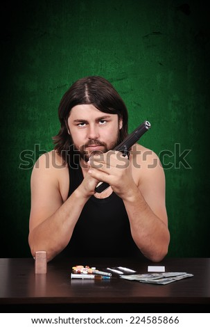 gangster man with a gun om green background - stock photo