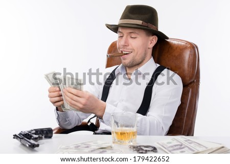 gangster sitting at a table counting money. on the table gun and brass knuckles - stock photo
