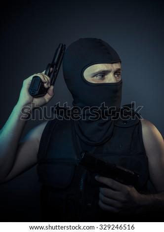 Gangster, terrorist carrying a machine gun and balaclava - stock photo
