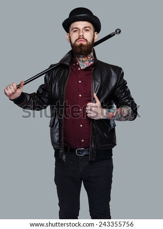 Gangster with cane and tattoes on his body - stock photo