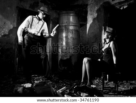 Gangster with gun and young women on the chear - stock photo