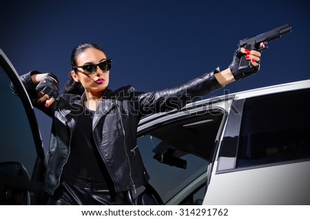 Gangster woman with gun near the car - stock photo