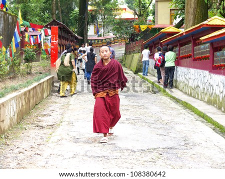 GANGTOK,SIKKIM/ INDIA-JUNE 12:Novice Lama walk out while tourists walk in turning the prayer wheels and praying for concentration and getting the merit at Enchey Monastery on June 12, 2012 in Gangtok. - stock photo