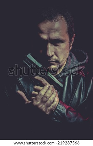 ganster, dangerous man with a gun, shooting - stock photo