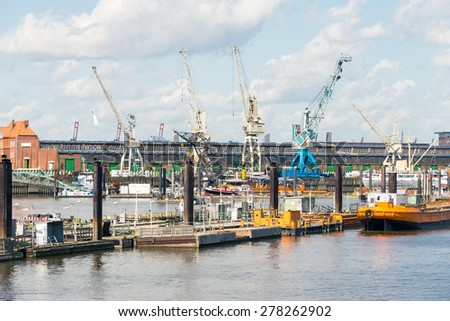 Gantry cranes at the quay in a harbor basin in the Hamburg district Kleiner Grasbrook. Here the Port Museum has an exhibit of old harbor equipment and harbor implement at shed 50a - stock photo