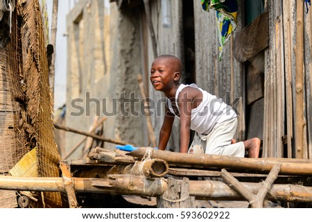 GANVIE, BENIN - JAN 11, 2017: Unidentified Beninese little boy plays near a house in a village over the lake Nokwe. Benin people suffer of poverty due to the bad economy.