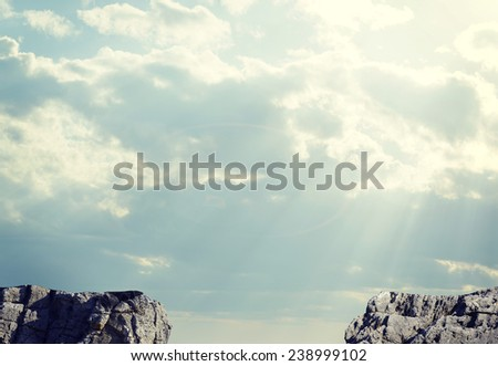 Gap in rocky pathway or chasm between two rocks. Sky and clouds as backdrop - stock photo