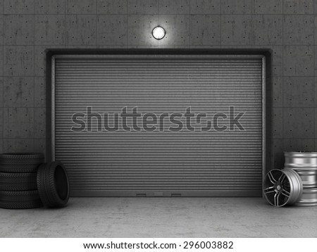 Garage building made of concrete with roller shutter doors, tires and rims. Garage concept. - stock photo
