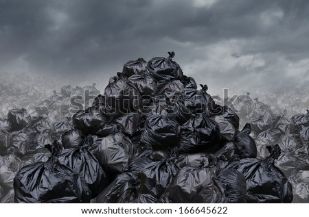 Garage dump concept as mountains of black trash bags with an unpleasant smell  in an infinite landfill heap landscape as a background of environmental damage issues on a foggy  dark cloudy scene. - stock photo