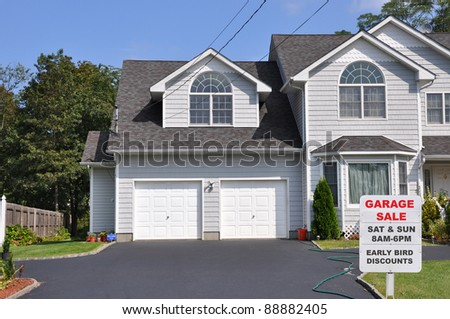 Garage Sale Sign on Black Top Driveway Edge in Front of Suburban Two Car Garage Home Sunny Blue Sky Day - stock photo