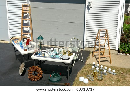 Garage sale with odd and ends objects for sale on tables at a suburban house yard driveway - stock photo