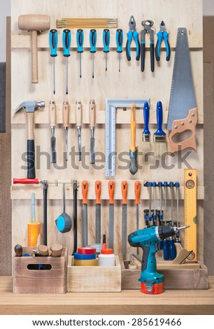 Garage tool rack with various tools and repair supplies on board and shelves. - stock photo