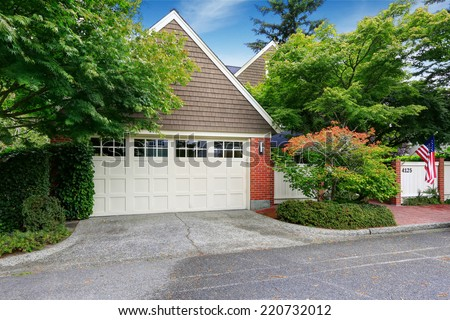 Garage with clapboard siding and brick trim. Real estate - stock photo