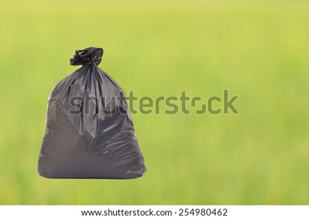garbage bag on green  nature blur background  - stock photo