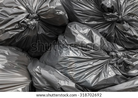 Garbage bags blacks stacked and ready to be picked. - stock photo