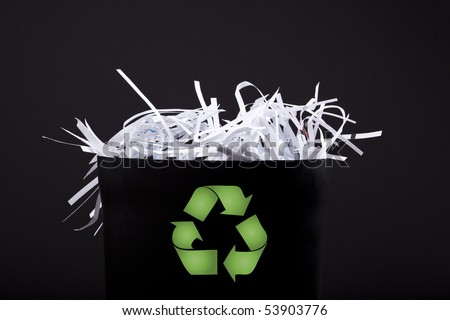 garbage bin with shredded paper and recycle symbol - stock photo
