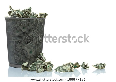 Garbage can full of money spilling over, left side - stock photo