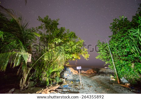Garbage collection on a tropical island. Night view with vegetation and stars. - stock photo