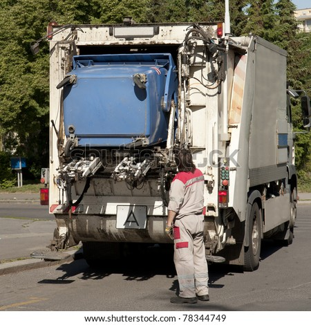 Garbage collector loading waste on the street - stock photo