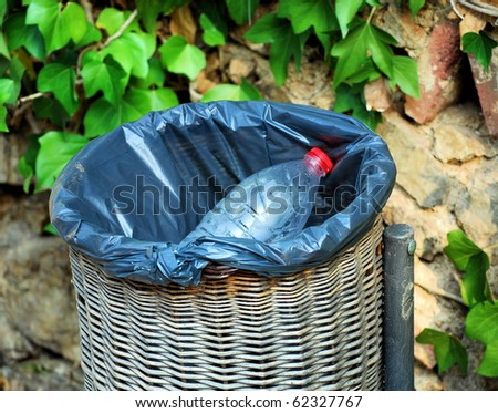 garbage container with a bottle in park - stock photo