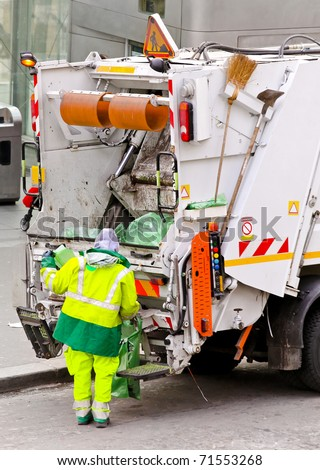 Garbage man at work at dump truck - stock photo