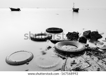 garbage on the beach in black and white - stock photo