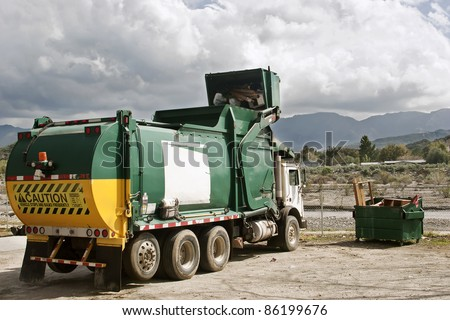 Garbage truck caught in action disposing trash. - stock photo