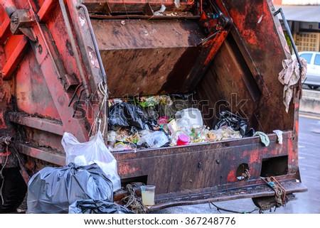 Garbage truck keeping garbage on urban street. - stock photo