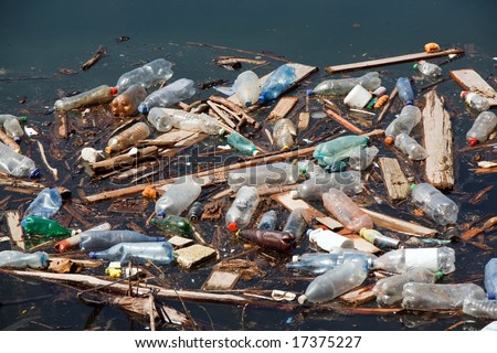 garbage with plastic bottles wood and other pollution on lake water - stock photo