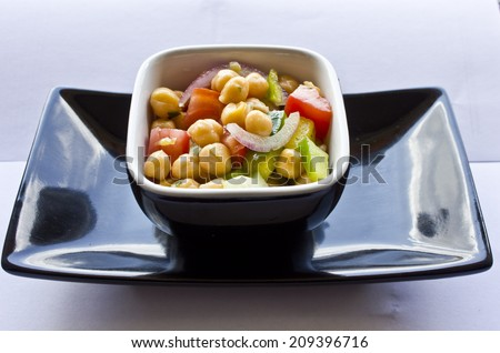Garbanzo Bean Salad. A fresh chickpea salad for the summer season, done with raw vegetables such as onion, green pepper, celery, tomato and parsley. An healthy an easy recipe! - stock photo