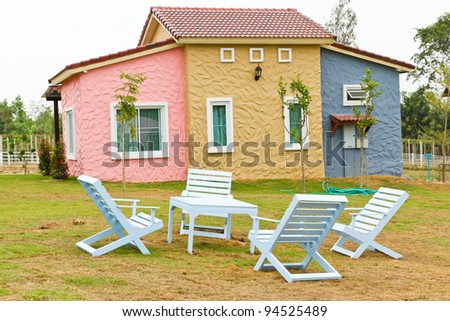 garden and home with white chairs and table on the grass - stock photo