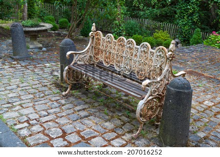 Garden bench on a cobblestone pavement in the courtyard - stock photo
