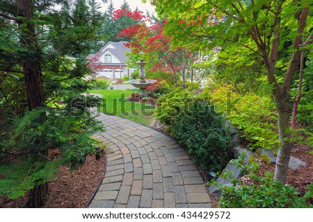 Garden brick paver path in frontyard with water fountain plants shrubs evergreen and deciduous trees landscaping - stock photo
