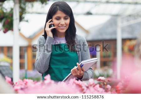 Garden center worker phoning while taking notes on flowers in center - stock photo