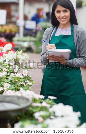 Garden center worker taking notes and smiling in the garden centre - stock photo