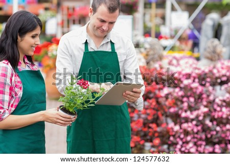 Garden center workers using tablet pc to check flowers in garden center - stock photo