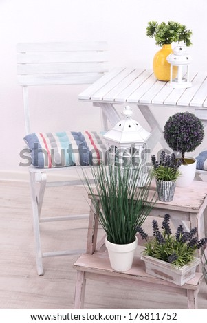 Garden chair and table with flowers on wooden stand on white background