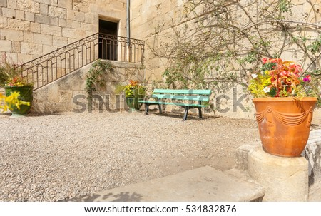 Garden courtyard surrounded by stone building wall with empty bench seat and pot plants