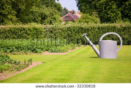 Garden decoration. Big watering can on the lawn