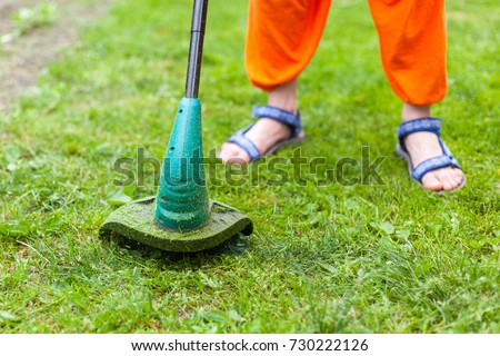 Garden equipment. Young woman mowing the grass with a trimmer