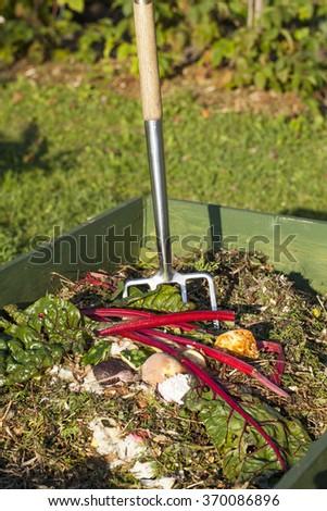 Garden fork in a compost bin. - stock photo
